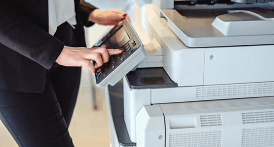 Woman office worker pressing button on printer