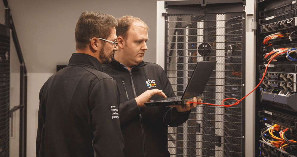 Men holding laptop next to servers in data centre
