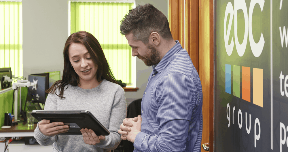 Man and woman in office holding tablet with Wi-Fi