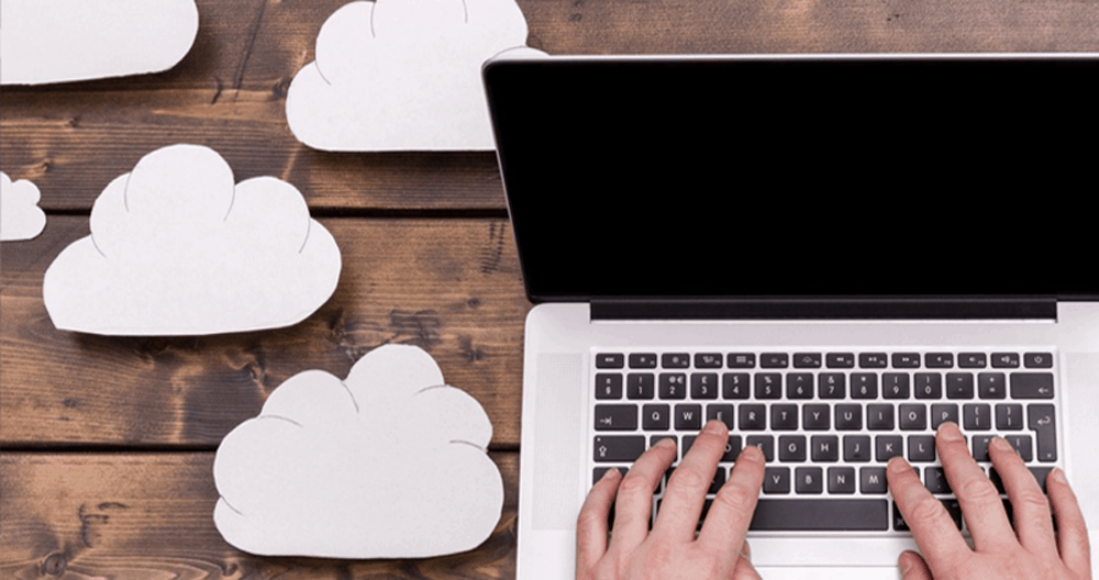 Laptop on wooden desk with cloud illustrations